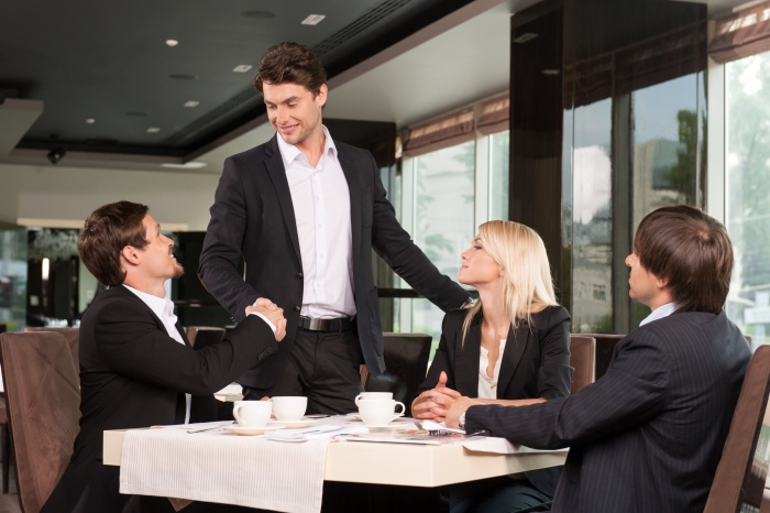 Handsome business man greeting group of people.